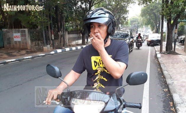 merokok sambil mengendarai motor